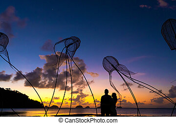 Figures of jellyfish on a background of a beautiful sunset. Couple hugs on a background of a fiery sunset. Tropical romance. Beach by the ocean