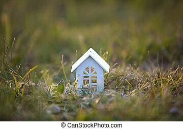 Figures of small white wooden houses on the grass close-up. The cottage is in a rural location and village, building, project, moving , mortgage, rent and purchase real estate. Copy space