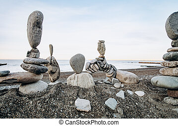 Figures of stones on the beach near the sea. Sea background and stone figures.