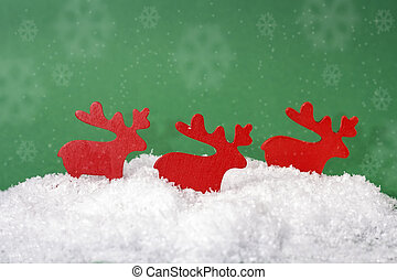 Figures of wooden christmas deer in the snow on a green background with snowflakes