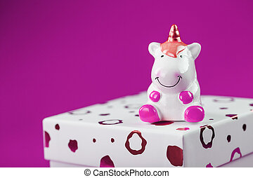Figurine of a unicorn on the box with a gift on a pink background.
