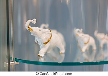 Figurine of an elephant on a glass shelf of a cabinet. Background in bokeh.