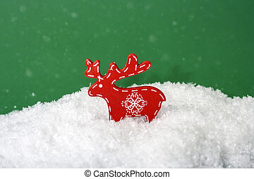 Figurine of wooden christmas deer in snow on green background with snowflakes