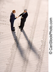 Figurines Of Two Businessmen Shaking Hands On A Financial Newspaper
