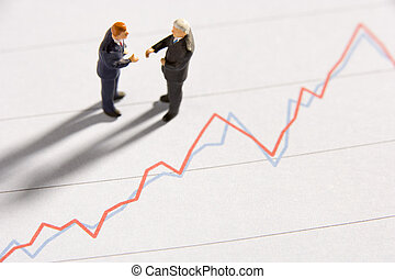 Figurines Of Two Businessmen Shaking Hands On A Line Graph