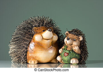 Figurines of two hedgehogs sitting on a reflective surface