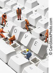 figurines posed on a keyboard - Worker figurines posed...