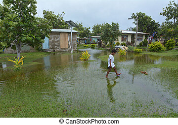 Fijian girl walks over flooded land in Fiji - Indigenous...