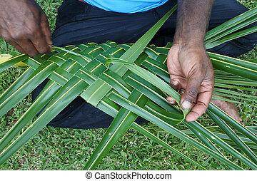 Fijian men create a basket from weaving a Coconut Palm leaves