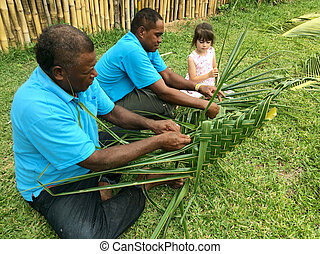 Fijian men teach young tourist girl how to create a basket from Coconut Palm