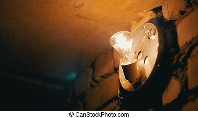 Filament Bulb Lights Up on a Stone Wall
