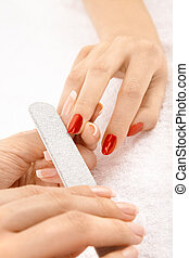 Professional processing of nails by a nail file, isolated