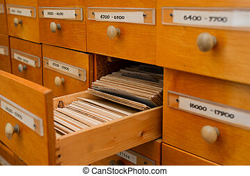 Files catalog with open drawer. Vintage wood cabinet in the library. Paper cards with information. Data archive