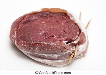 Raw beef tenderloin medallion wrapped in pork bacon