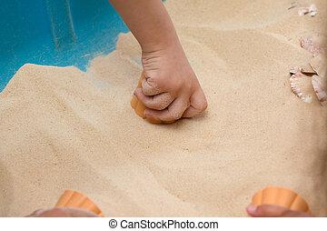 filho jogando, areia