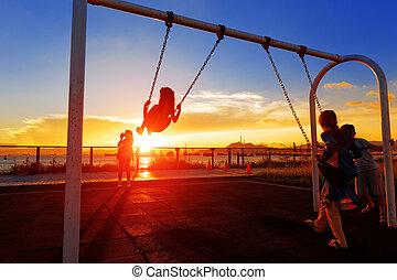 filho jogando, balanço, contra, pôr do sol