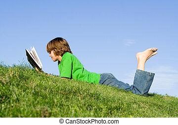 filho lê livro, ao ar livre