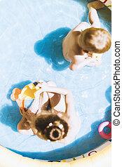 filhos jovens, jogar brinquedos, dentro, um, inflável, piscina