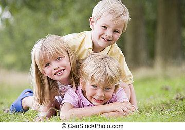 filhos jovens, três, ao ar livre, sorrindo, tocando