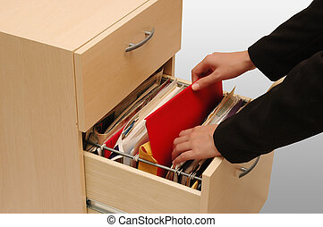 Filing Cabinet - woman putting back an important file into...