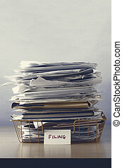 Filing Tray Piled Up with Papers - A filing tray with label,...
