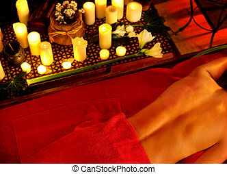 Filipino massage of woman in spa salon. Girl on candles background.