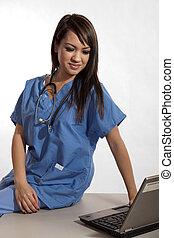Filipino nurse doctor working on laptop