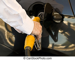Fill up tank - Man wearing protective gloves filling up his...