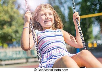 fille souriante, amusement, balançoire, avoir, cour de récréation