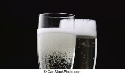 Filled with two glasses of champagne with white bubbles on a black background. Close up