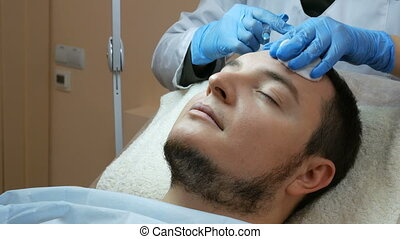 Filler injection for male face. Cosmetic surgery facial in beauty clinic.
