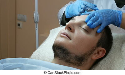 Filler injection for male face in beauty clinic.