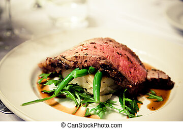 Fillet of Beef steak and vegetable with gravy splashed around on white plate