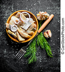 Fillet of salted herring with herbs and garlic cloves.