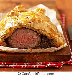 Fillet Wellington in puff pastry on wooden table