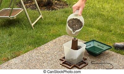 Filling a Bird Feeder - Male person filling a bird feeder on...