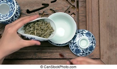 Filling a brown teapot through a funnel. Porcelain chinese...