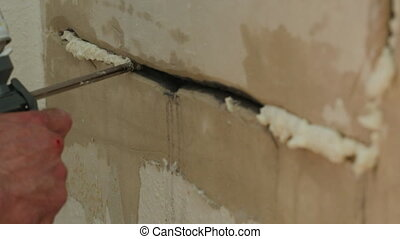 Filling a wall crack with foam