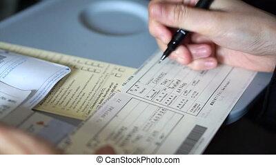 filling custom immigration form - Tourist hand filling...