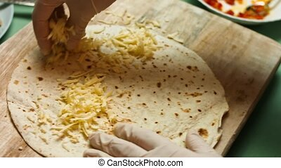 Filling flour tortilla with grated cheese. Process of making mexican quesadillas with cheese and vegetables. Artistic shooting, macro.