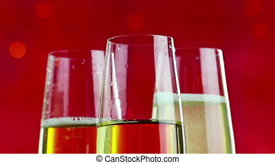 filling flutes of champagne with golden bubbles against red bokeh background, holiday concept