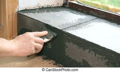 Filling gaps between tiles with grout - Hands of tile worker...