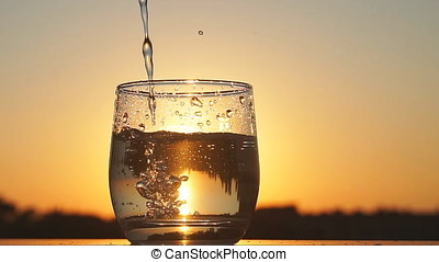 Filling glass with water at the sunset, Slow motion
