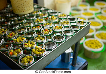 Filling of glass jars with pickled olives