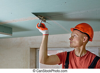 Filling the seams plasterboards. - The worker is filling the...