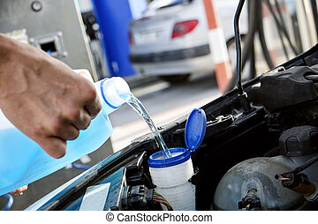 filling the tank of windshield washer fluid
