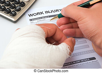 filling up a work injury claim form with a wrapped hand,...
