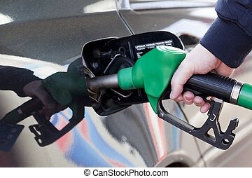 filling up car with gas - man filling up car with fuel at...