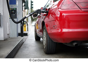 Filling up with gas. - Red car at gas station being filled ...