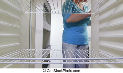 fills food into refrigerator - Housewife fills food into...